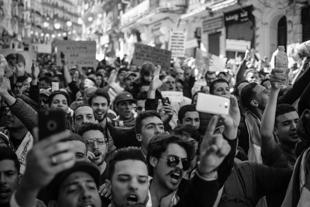 A group of people, all crowded together. They seem to be in a protest and are holding up phones. Some look as though they are yelling and pointing at something.