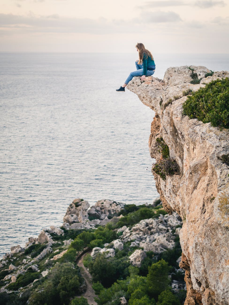 Person sitting on the edge of a cliff overlooking the ocean.